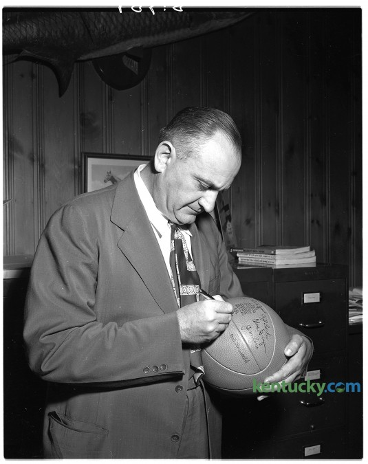 Legendery University of Kentucky basketball coach Adolph Rupp autographs a basketball that will be awarded to youth organizations in state for the sale of E bonds. Published in the Lexington Herald-Leader June 26, 1949. Herald-Leader Archive Photo