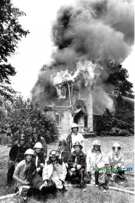 A group of firefighters pose in front of a burning house in rural Fayette County during a fire school exercise on June 2, 1981. The 86th Annual Kentucky State Fire School is in session in Lexington this weekend, June 3-7 where more than 1,200 firefighters and first responders are in attendance. Photo by Charles Bertram | Staff