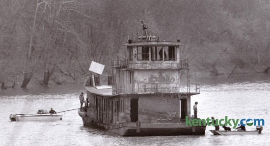 Two small boats helped maneuver a larger boat down the Kentucky River near Boonesboro November 18, 1986. The larger vessel had been submerged for nearly a decade and was raised and moved by Eddie Carter of Winchester. Carter planned to refurbish the boat. Photo by Gary Landers