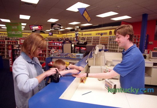 Marley Sommer, 8, reaches over the counter June 1, 1999 to hand money to clerk Patrick Watson at the Blockbuster video rental store on Richmond  Rd. At left is Marley's mother Melissa Sommer. Blockbuster closed all of its retail locations in Jan. 2014. Photo by David Perry | staff