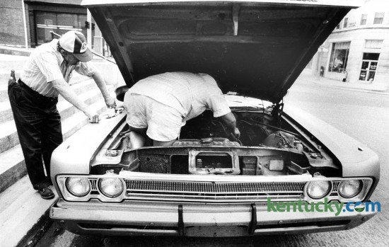 Russell Templin went right to work on his car, Aug. 17, 1985, after it broke down on Main Street in Winchester. He had to get underneath the hood to get at the problem. His father, Harry, watched and offered advice while he worked. Photo by Bruce Thorson | staff