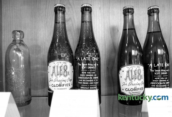 """A display of Ale-8-One bottles in the lobby of the Winchester plant, July 2, 1990. The bottles shown are returnable bottles that were used from 1940-1959. According to spokeswoman Samantha Jackson, the company isn't sure why they chose """"It Glorifies"""" on the front label but there are many differing opinions. That saying was last used on a returnable bottle in 1983. The current returnable bottle features the nutrition information on the reverse. Eighty-nine years after it was introduced at the Clark County Fair, Ale-8-One's packaging and branding is getting a 21st-century update. Photo by Stephen Castleberry 