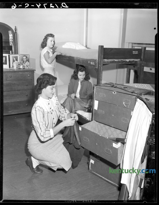 University of Kentucky students move into their dorm room in Patterson Hall during orientation week activities, Sept. 1949. Pat Moore, foreground, unpacks,  Marian Ferguson, rear,  made up her bunk and Mary Jo Cundiff applied polish to her nails.  Published in the Herald-Leader September 18, 1949. Herald-Leader Archive Photo