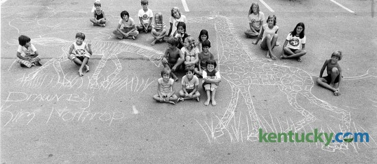 Neighborhood kids sit around a chalk drawing 13-year-old Kim Northrop made on the parking lot of the Cloister Apartemtns on Pimlioc Parkway in Lexington July 29, 1976. The kids blocked off traffic to the parking lot so a photographer could get a picture of the zebra and giraffe. Photo by Ron Garrison | staff
