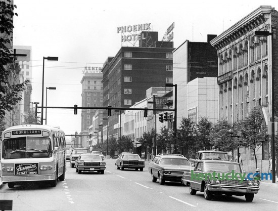 Traffic on Main Street in downtown Lexington, June 11, 1976. The photo was taken from Cheapside street looking east. The Phoenix Hotel was demolished in 1981 and 1982 by Wallace Wilkinson, who had planned to build the World Coal Center skyscraper on the site. It was never built, and the site eventually became the Park Plaza Apartments and Phoenix Park.  Photo by Frank Anderson | staff