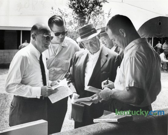Looking over the sales catalog at Keeneland in July of 1963 are Leslie Combs II, founder and owner of the Spendthrift Farm, Brownell Combs, Leslie's son, John S. Knight, then owner of the Knight Newspaper chain which would later include the Herald-Leader, and an unidentified horseman. The two day Summer Yearly Sale was held on July 22-23, 1963.  The Keeneland November Breeding Stock Sale begins today and runs through November 13. Herald-Leader Archive Photo