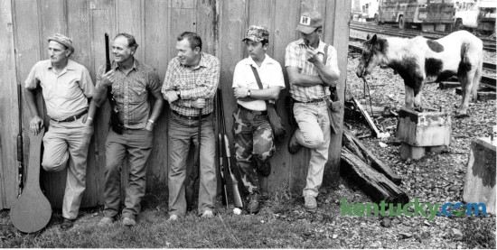 Taking shelter from a heavy rain at the Mt. Sterling Court Days on October 20, 1985 are, from left, Milford Bivens, Flemingsburg, Tony Wainscott, Lawrenceburg, Gene Gregory, Stamping Ground, Shelby Burgin, Richmond and John Fortune, Mt. Sterling. The annual gathering started in 1794 and took place when the Circuit Judge came to town to try criminals. People came from miles around to sell crops, trade horses and mules and other farm animals as well as swap goods and services. Guns and knives were among the top items traded. It continues to be one the largest outdoor festival in Kentucky. Photo by Gary Landers