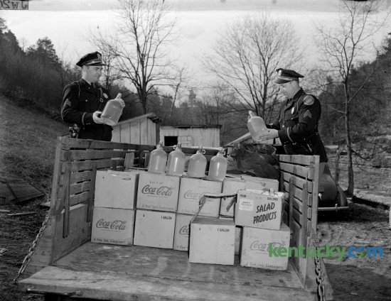 Two State Highway Patrol officers posed with some of the confiscated moonshine after Federal agents raided a the production facility at Fox Gap on March 14, 1945. The location of the still was on the side of a creek near the old Fox Gap school on the Frankfort-Lawrenceburg pike, three miles from Frankfort. Officials stopped this truck, loaded with 176 gallons of whiskey, as it was on it's way to Lawrenceburg.  Four suspects were taken into custody. Published in the Lexington Herald March 15, 1945. Herald-Leader Archive Photo