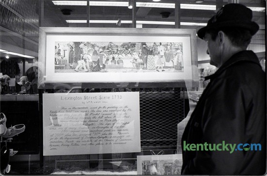"""W.W. Mathews (cq) of Nicholasville, Ky viewed the painting of a mural on display in the window of Hymson's  Department Store on Main Street. Artist William P. Welsh did a re-painting of his original mural, """"Lexington Street Scene, October 1793"""" that had been located in The Kentuckian Hotel on High Street. During the razing of the hotel, the mural was accidentally destroyed. The Downtown Lexington Association had prints make from the painting. 250 signed and numbered prints sold for $100; while 4,750 unsigned prints were sold for $35. Lexington Herald-Leader, Jan. 12, 1975. Photo by E. Martin Jessee 