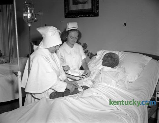 """Monroe Smith, a former slave who was born August 15, 1848, on a farm near Bardstown, was a patient at the St. Joseph's hospital, where he was admitted for treatment for a chest condition in August 1947. With Smith are Sister Agnes Sienna and nurse Beaturice Chumley. Smith, who was owned by a Hill family, grew up as a field laborer and remembered that he was hoeing corn when the news of Lincoln's election to the presidency came. Because the Hills were so kind to their slaves, many stayed on even after they were freed, Smith said. He left after four years and worked as an odd-job man around Bardstown until he was hired as a gardener by the Sisters of Charity of Nazareth. Smith says he never married because """"whenever I should have been out courtin' I was hiding stock and farm produce to keep them from the Rebel and Yankee armies.""""  Published in the Herald-Leader August 17, 1947. Herald-Leader Archive Photo"""