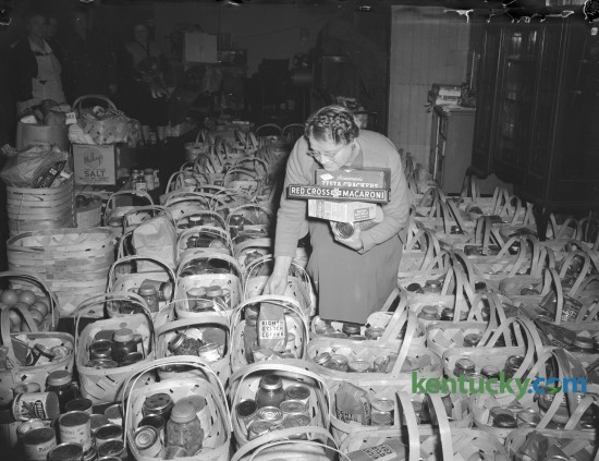 Mrs. Roy Jennings, 370 Bucoto Court, shown filling one of 400 baskets of food collected by Goodfellows Club of Everybody's church. Published in the Lexington Herald-Leader December 23, 1945. Herald-Leader Archive Photo