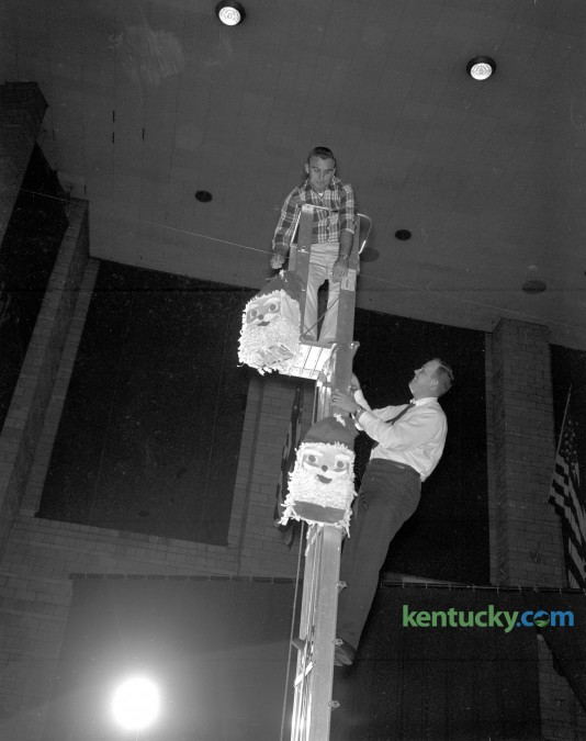 Jack Gallagher, left, and Jim Flynn, members of the Lexington Junior Chamber of Commerce are shown hanging some of the decorations for the annual Christmas party for all Central Kentucky children, set for Sunday afternoon December 10, 1961. Herald-Leader Archive Photo