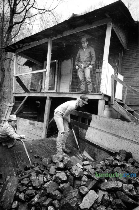 Oliver Meade watched from his porch as Jellen Meade, left and Harold Meade unloaded about 3 tons of coal at his home in Deane, Ky. on December 4, 1990. The photo ran with a story about a federally funded program that provided free coal for needy families in Leslie, Perry, Letcher and Knott counties. Photo by Charles Bertram | Staff