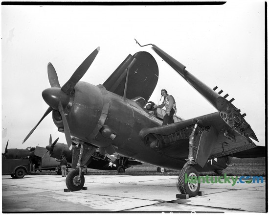"Lieutenant John Mason, United States Naval Reserve, is shown climbing into his plane, an SB2C Helldiver, Oct. 22 1945 at Blue Grass Field in Lexington, where he and other members of the Navy Victory squadron presented an exhibition. 20 Naval planes flew a ""Navy Flying Might"" air show as part of Fayette County's Vickty War Bond campaign. The insignia on the plane show that Lieutenant Mason destroyed three Japanese planes on the ground, sank two ships (a destroyer and a freighter-transport) and participated in 30 bombing missions. Published in the Lexington Leader October 23, 1945. Herald-Leader Archive Photo"