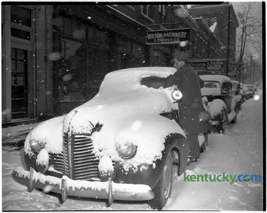 An unidentified man cleaned the snow off his car in front of Wilson Machinery and Supply Company, 139 North Mill Street, after Lexington received four and a half inches on December 5, 1945. Published in the Lexington Leader December 6, 1945. Herald-Leader Archive Photo