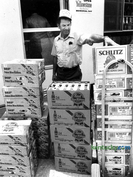 "Don Bailey, owner of Parkway Liquors near Salyersville in Magoffin County, inspects the latest beer shipment June 3, 1982. This photo ran with a story updating how alcohol sales are going after Magoffin County magisterial District 3 voters overwhelmingly said yes to liquor sales. The vote split the county in half along KY 7 with the south side of the county allowing liquor sales. Nealry all of the district's five liquor stores and 16 beer carryouts were located along KY 7. Many of them popped up as small, plywood-type buildings. A clerk at Parkway Liquors, located close by a Mountain Parkway exit, called them ""walk-in freezers with cash registers."" Today, all of Magoffin County is wet. Photo by Charles Bertram 