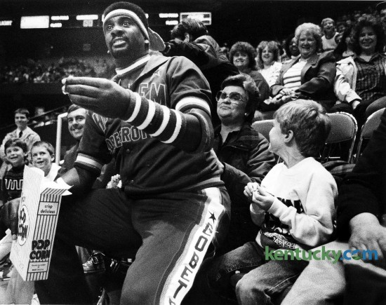 """Harlem Globetrotter center """"Sweet Lou"""" Dunbar gots spectator's view of action from Jan Shuff's lap before his team played the Washington Generals April 9, 1989 in Rupp Arena. Like they usually do, the Globetrotters beat the Generals in front of 4,000 fans at the Lexington arena. Fans, some still dressed in their Sunday best, flocked to the game anticipating the Globetrotters' usual antics. The team did not disappoint them. Constant banter between center """"Sweet Lou"""" Dunbar and announcer Jeff Beck and the referees kept young and old in hysterics. """"What a clown, what a clown,"""" one fan repeated as Dunbar ridiculed the referees, the Generals players and spectators. Photo by David Perry 