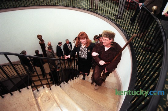 "House Democratic Leader Greg Stumbo of Prestonsburg climbed the steps in the Old Capitol in Frankfort with Charlotte Ellis, his chief of staff Jan. 6, 1998 during the opening day of the General Assembly. As the 20th century drew to a close, lawmakers decided to meet in the same building where legislators gathered at the start of the century. Wearing buckskin britches and coonskin caps, Stumbo and about a dozen fellow Eastern Kentucky Democrats referred to themselves as ""The Mountain Caucus"". The group wore the pioneer garb, borrowed from a Central Kentucky theater troupe, to symbolize a feeling that Eastern Kentucky has been left behind by the rest of the state and the lawmakers' determination to get more money this session for their region's needs. Photo by Charles Bertram 