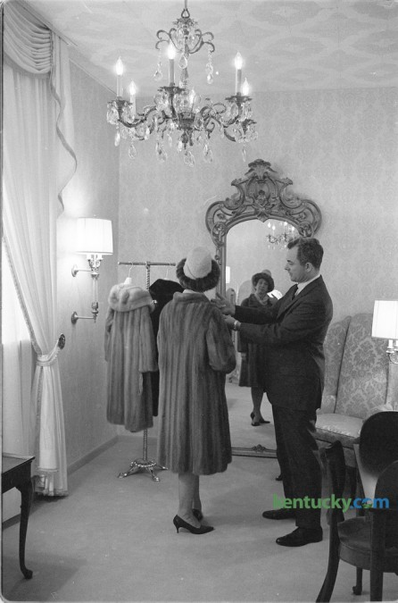 "The president of Embry's, William R. Embry Jr. helped a customer decide on a  fur coat in the second floor Crystal Room, which provided seclusion for those wishing to view furs. The photo ran with a story about the grand re-opening of their remoded downtown store, located at 141 East Main Street, in December 1966. Embry's, known as Kentucky's premier fur and fashion boutique first opened in 1904 specializing in hats and the ""finest ladies fashions"". The business continues today and is now located in the Lansdowne Shoppes. Published in the Lexington Herald-Leader December 4, 1966."