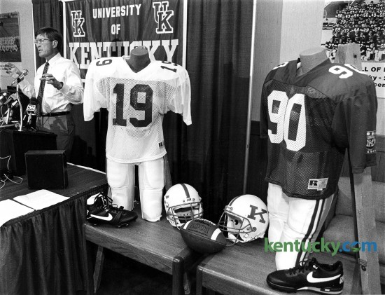 "First-year University of Kentucky football coach Bill Curry unveiled new uniforms a week before his freshmen reported for pre-season practice, July 27, 1990. A pair of mannequins were on hand, sporting the Wildcats' new less-means- more uniforms, complete with the player-popular black footwear. Curry said there was no major significance in the fact that the new coach decided to place his first Kentucky team into a set of subtly different duds. And no, said Curry, he did not try to pattern UK's new attire after any particular team, save maybe his old Baltimore Colts. ""I think the uniforms look good, and that's all we need,"" said the coach. Simplicity being the Curry look for the '90s. Basics remain - white helmets with a blue ""K"" on the side, blue jerseys, white pants. Gone are the two blue stripes down the center of the helmet, replaced by a single stripe. Gone are the blue pants. The Cats will wear white trousers home and away. Gone are stripes on jersey sleeves, replaced by a single patch commemorating the school's centennial football season. Gone, too, are white shoes, replaced by your basic black models. Because, said Curry, ""The players like the black shoes."" Photo by Charles Bertram 