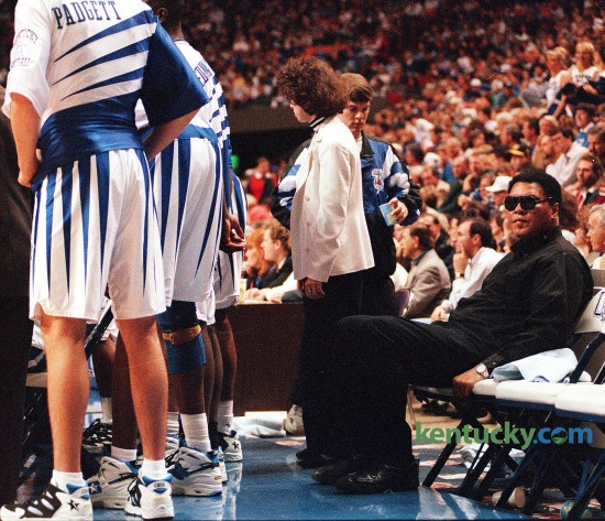 """Three-time heavyweight boxing champion Muhammad Ali sat on the Kentucky bench during the Cats' game against Florida, Feb. 18, 1995 at Rupp Arena. Ali attended the game as part of a one-day promotional visit to Lexington for a play, Ali, which ran later that month at the Opera House. A playful Ali met the UK players in the locker room before the game. """"He said I'll take you all on,"""" Jeff Sheppard said. Ali also threw some punches. """"I jabbed at Anthony Epps,"""" Rodrick Rhodes said. """"He told Epps he reminded him of Joe Frazier."""" UK coach Rick Pitino noted that the UK players were too young to remember Ali in his fighting prime. """"For me, personally, it was a thrill of a lifetime,"""" the UK coach said of Ali's presence on the bench. Ali and Sheppard shared a laugh while the game neared its dramatic finish. With 1:23 left and the Cats ahead 77-75, Sheppard was fouled but had to leave the game because of blood on his nose. Chris Harrison entered the game and made both free throws. As Harrison shot and team physician Dr. David Caborn worked on a cut on Sheppard's nose, Sheppard turned to Ali and said something. Ali and Sheppard then smiled. """"I told him I got punched in the nose,"""" Sheppard said. Photo by Mark Cornelison 