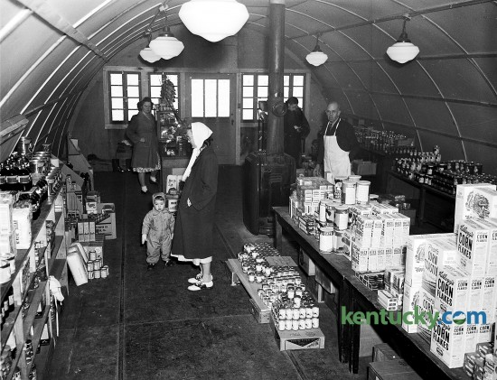 Interior view of the community grocery store in Cooperstown on the University of Kentucky campus, Jan. 1948. Cooperstown was a village of apartments, built in 1946 to house veterans who enrolled at UK. C. A. Shields, manager, is pictured in a white apron behind the counter. The grocery, which opened on Jan. 16, 1948 to service the more than 500 students veterans and faculity familes living in the housing complex, was a converted Army quonset hut. Published in the Lexington Leader January 23, 1948. Herald-Leader Archive Photo