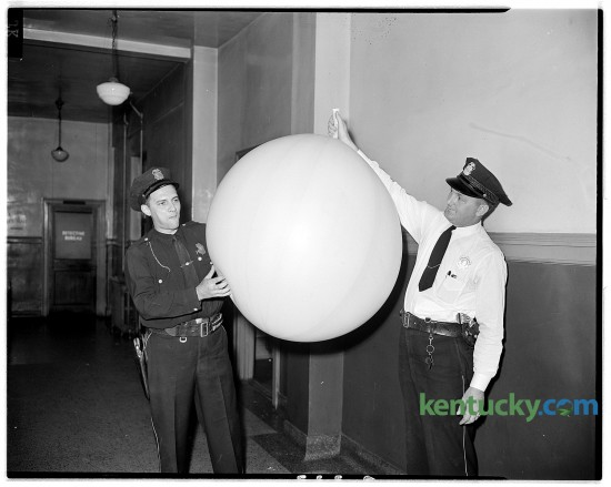 Lexington patrolmen Robert Duncan, left, and Stanley Hadley examine a large rubber balloon which landed on North Mill Street near Second Street on the evening of Aug. 29, 1945. Residents in the area were frightened by the possibility it may have been a Japanese balloon bomb. A small crowd of people kept a safe distance while officers examined the balloon. The police took the balloon to their headquarters where they deflated it and discovered it contained natural gas. No identifying marks were visible on the balloon and officers were puzzled as to its possible origin. Published in the Lexington Herald on Aug. 30, 1945. Herald-Leader Archive Photo ****8/30/1945***on Page O.332