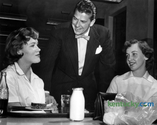 Screen and TV star Ronald Reagan met some of the employees  at the Lexington Lamp Works,  201 Rosemont Garden, during a tour of the plant  on Friday night, March 25, 1955. Here Reagan chats in the lunchroom of the  Lexington Lamp Works with Gretchen Boone (left), final inspector of  headlamps, and Bettye Watts, a tapper. A.D. Dixon was the plant manager at  the time. Reagan was the program supervisor of the General Electric Theater television series and came to Lexington  to visit two GE plants. He had breakfast that Friday morning at the Campbell  House with executives of the General Electric Co. and the Lexington  Herald-Leader. Photo published on Sunday  March 27, 1955. Photo by  E. Martin Jessee | Staff