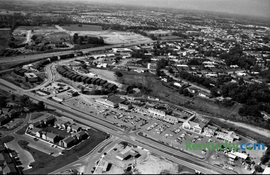 Aerial view of the Lansdowne Shopping Center in August of 1973. Tates Creek Road runs diagonally near the bottom of the photo, while New Circle Road is seen cutting left to right in the top third of the image. A portion of the Merrick Place Apartments is at the lower left. Some of the businesses occupying the shopping center, from right to left, included, Lansdowne Exxon, The Lansdowne Shoppe liquor store, Norgetown Laundry & Cleaning, Big B Cleaners, Henri's Fashions, First Federal Savings & Loan, Governor's Table restaurant, Begley Drug Company, First Security National Bank and Trust Company, Hallmark Colony of Cards, Pet Gallery, Lexington Academy of Dance, Stretch & Sew Fabrics, Angelucci's men's ware, Gingiss Formalwear, Lansdowne Florist, Line and Shot sporting goods, Lansdowne Veterinary Clinic, Lexington Travel Center, Lansdowne Barber Shop, Timothy beauty salon, Baskin-Robbins Ice Cream, and the A&P grocery store. Photo by  John C. Wyatt | Staff