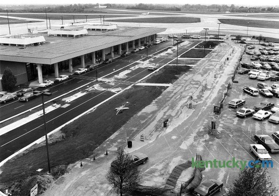 A $1.5 million project to repair deteriorated roads at Blue Grass Airport was nearing completion on Oct. 15 1985. The airports roads had deteriorated because of increased traffic volume, airport executive director Jim Brough said at the time. The improvements included rebuilding the entrance road to the airport, incorporating curbing and gutters with storm sewers, building a four-lane divided road leading into the airport, adding an interior circulation loop to the terminal, and improving intersection designs. Less than two years later, in September 1998, ground was broken on a $12 million expansion to double the size of the terminal that included new elevators and escalators, a restaurant and a third-level observation room. The first level of a $12 million, three-level parking garage opened more than 10 years later, in July 1999, in the area shown on the right side of the photo. The two upper levels, which were for long-term parking, opened the following October. The garage added more than 700 parking spaces, from fewer than 1,200 to nearly 2,000. Photo by Ron Garrison | Staff