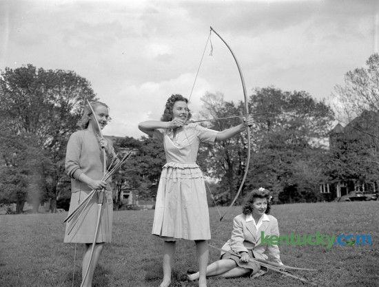 Three University of Kentucky co-eds practiced archery on campus in May of 1944. From left are Miss Elizabeth Carey, Miss Carolyn Gilson and Miss Anne Smith. Published in the Lexington Leader May 6, 1944. Herald-Leader Archive Photo