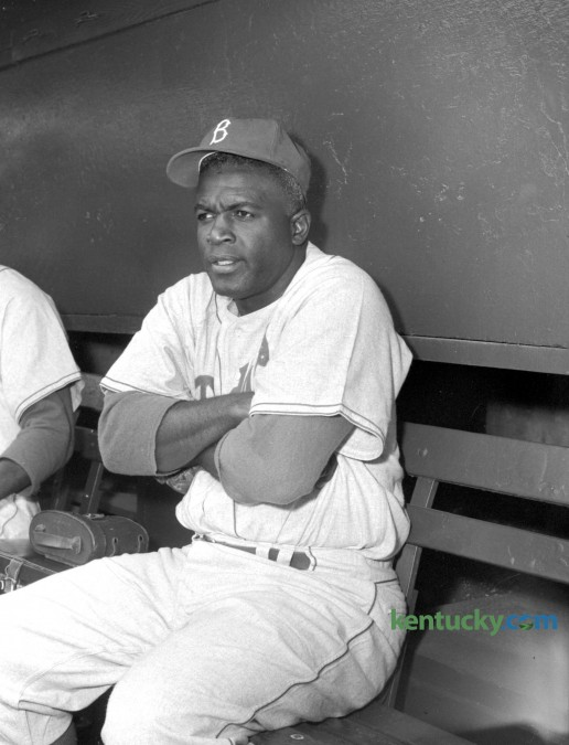 "Brooklyn's Jackie Robinson shivers in the dugout as the Brooklyn Dodgers played the Milwaukee Braves in an April 9, 1956 preseason game in Louisville. The temperature was 44 degrees at game time at Parkway Field. The California native joked, ""Now I know why they call it blue grass. It's frozen!"" This was the beginning of the 37-year-old Robinson's last season in professional baseball. Published in the Lexington Herald April 10, 1956. Herald-Leader Archive Photo"