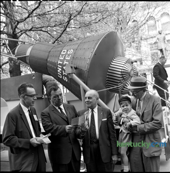 As part of the Freedom Bond Drive, a duplicate of Col. John Glenn's Mercury 7 space capsule was displayed in Cheapside Park on Friday April 27, 1962. Posing in front of the capsule was Bill Staton of the Lexington Jaycees, Robert Stilz, county savings bond sales chairman, County Judge Bart Peak and Lexington Mayor Richard Colbert, holding his son Richard. The primary purpose of the space capsule's visit to Lexington was to remind local residents of the Freedom Bond Drive and to urge them to invest in the bonds as well as giving them some idea how some of their taxes for defense are invested.  Published in the Lexington Leader April 28, 1962. Herald-Leader Archive Photo