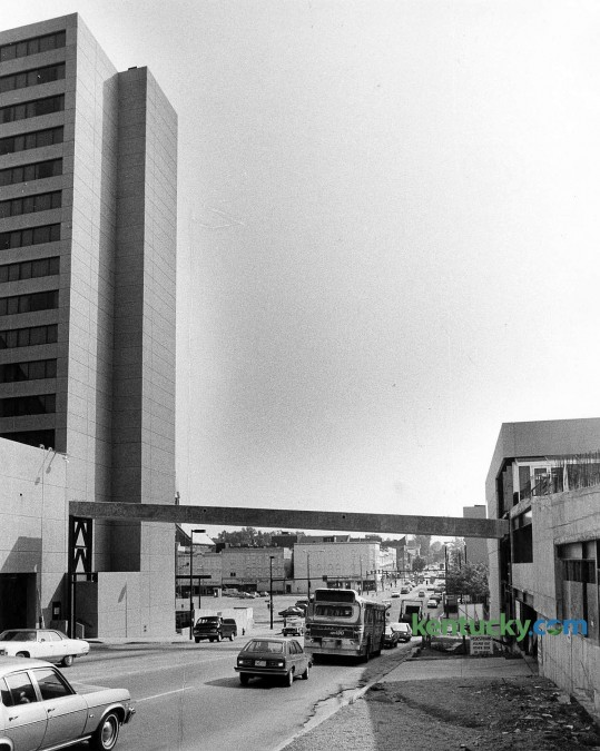 Construction of the skyway crossing South Broadway in downtown Lexington, connecting the Hyatt Regency, shown at left, and Kincaid Towers, July, 1979. The concrete span, first in a series of skyways over downtown, is 100 feet long and nine feet wide. It is about 30 feet above South Broadway at its mid-point. The $100,000 project would wrap up with a lerge covering of aluminum and Plexiglas and opened when Kincaid Towers construction was completed later in the fall of 1979. The photo was taken looking east down South Broadway. In the background, just above the bus is what is now The Square. To the left of the bus is a parking lot which would later become Triangle Park. Photo by Frank Anderson | staff