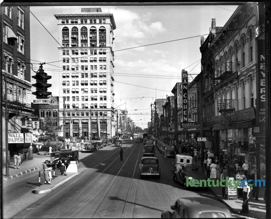 "Main Street, downtown Lexington, circa summer 1938. Rails run down the street, but around this time streetcar service was discontinued in Lexington. Like most American cities, as roads were improved and more people bought automobiles, trolley tracks were pulled up or paved over. Motor buses took over the steadily declining demand for public transportation. In the lower left corner of the picture you can see two women and a child waiting for the bus that coming towards them. Along the left side is what is now Cheepside Park. Further down is Lexington's first skyscraper, the First National Building. Built in 1913, it is now a 21c Museum Hotel. The buildings on the right include a Woolworth five-and-dime store and clothing store B.B. Smith & Co., whose sign said it was ""Correct Appareral for Women & Misses"". This is now the site of the Lexington Financial Center, or more commonly known as the ""Big Blue Building"". Herald-Leader archive photo"