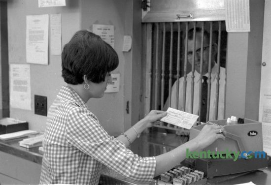 Suzanne E. Hudson helps a customer in the Lexington Post Office in September 1966.  Hudson became the first female window clerk to work at the office since 1952.  She was among 27 women employees, including two carriers, several clerks, stenographers, and secretaries. In 1960, there were only six women with the post office. Photo by John C. Wyatt | staff