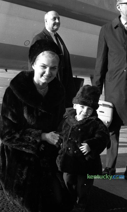 18-month-old Gregory Popan of Hazard greets Miss America 1969 Judith Anne Ford when she got off the plane at Blue Grass Field, Feb. 20, 1970. Popan was at the Lexington airport to greet his grandparents when he stumbled upon the beauty queen. Ford was in town to be the master of ceremonies for the Miss University of Kentucky pageant. Published in the Lexington Herald and The Lexington Leader, Feb. 21, 1970.