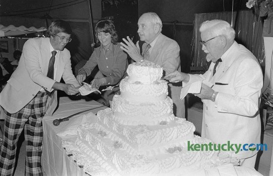 Former University of Kentucky basketball coach Adolph Rupp, center, and Kentucky Fried Chicken founder Col. Harland Sanders, right, cut a cake in observance of Lexington radio station WJMM's first anniversary, July 25, 1974. Also participating in ceremonies in the Gospel Music Tent at Blue Grass Fair were the Rev. Jack Mortenson, station owner, and Ms. Kay Chaney, assistant to the station manager. The radio station, a Christian teaching-talk station, has now served Lexington and surrounding communities for over 40 years. At the time of this photo, Rupp was 72 and had been retired for two years. Sanders was 83 at this time, 10 years since he sold the company to a group of investors led by John Y. Brown, Jr. and Jack C. Massey for $2 million. Published July 26, 1974 in the Lexington Leader. Herald-Leader Archive Photo