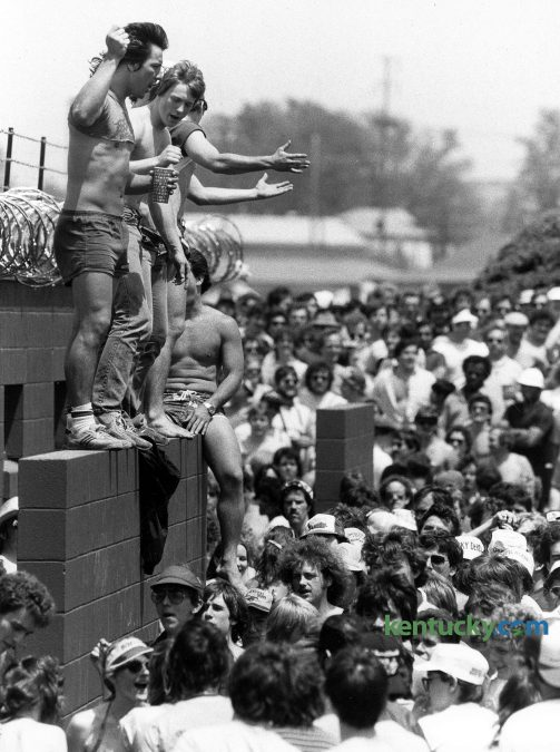 Despite the threat of barbed wire fence, infield patrons climbed up the outside of a restroom entrance May 7, 1983 at Churchill Downs. Not more than 100 yards away were several dense clumps of bushes that served as alternate restroom space as the afternoon wore on. Photo by CHarles Bertram | staff