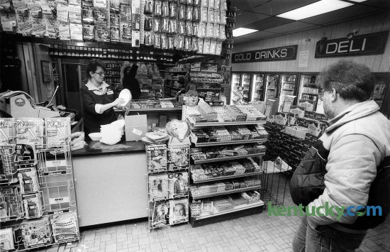 Interior view of a SuperAmerica convenience store on Winchester Road in Lexington Feb. 10, 1987. Some of the items for sale above the counter include film and flashes for cameras. To the right is a display of candy bars that include Hersey bars, M&M's and Snickers just to name a few. On the bottom and right side of the counter are such magazines as People, TV Guide and Sports Illustrated, which features Kentucky-native Phil Simms on the cover after his win in Super Bowl 21. In 1997 after the merger of Marathon and Ashland Petroleum, many SuperAmerica stores across the nation were renamed Speedway. In 2011 Marathon sold its SuperAmerica stores. Today Speedway and SuperAmerica are unrelated chains. Most of the SuperAmerica's are located in the midwest. Photo by Steven R. Nickerson | staff
