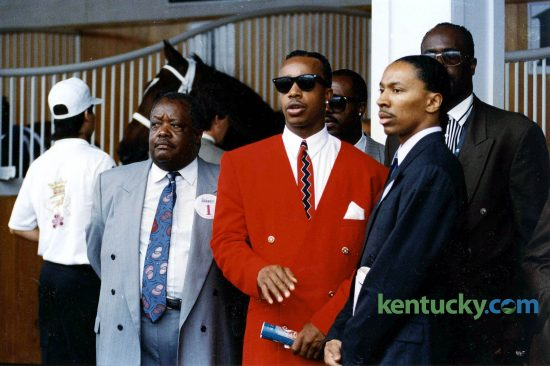 """Rapper M.C. Hammer, center, surrounded by family in the paddock just before the 1992 Kentucky Derby. In the background is Hammer's horse, Dance Floor, who finished third in the Run for the Roses. Hammer rose to fame in 1990 with his song """"U Can't Touch This."""" Photo by Charles Bertram 