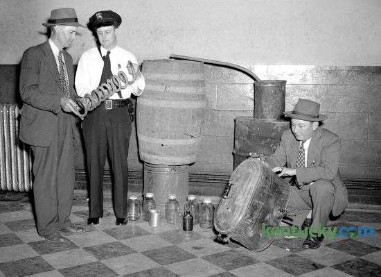 Jessamine County Sheriff Harvey Partin, left, and Nicholasville Police Chief Carl Bruner examine parts of confiscated 50-gallon moonshine still, May 14, 1947. The equipment consisted of a sour mash barrel, complete worm, condensing barrel, boiler, 12 half-gallon jars and several half-pint bottles. The officers said it had recently be used. Three days later, a jury of 10 men and two women convicted two men with possessing the still. County Judge T.R. Guyn gave them each $250 fines and three months in jail. Published in the Lexington Leader May 15, 1947. Herald-Leader Archive Photo