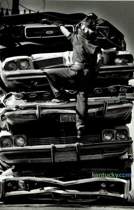 Donald Baker, with Baker Iron and Metal on Manchester Street, climbed up a stack of crushed autos on September 28, 1981. The cars were on a flat bed truck and he was securing them with a cable before being taken to a recycling center out of state. Photo by Ron Garrison | Staff