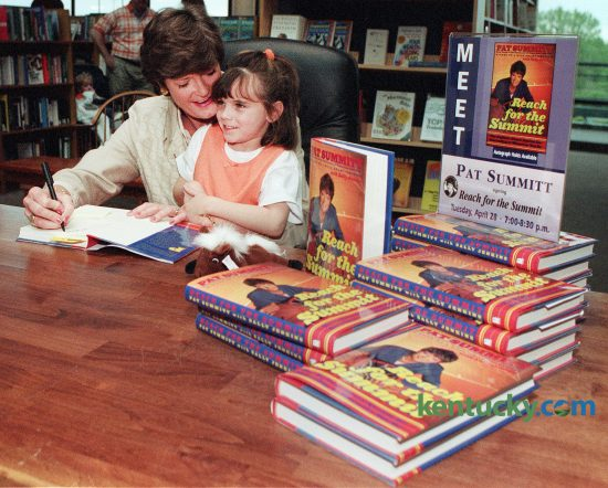 Six year-old Kathleen Dawson of Lexington sets on Pat Summit's lap as she autographs a copy of her new book Reach For the Summit,  for Dawson's mother.  Dawson brought Summit a KY Derby Beanie Baby for her son Tyler.  April 28, 1998