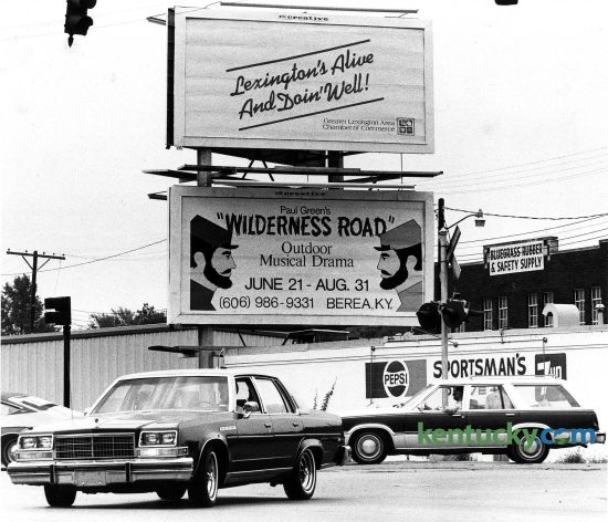 "A billboards at the intersection of Winchester Road and Walton Avenue proclaimed ""Lexington's Alive and Doin' Well"", Aug. 1, 1980. Behind traffic is the Sportsman's Drive-In Liquor store, which is now Locals' Craft Food and Drink. Photo by Ron Garrison 