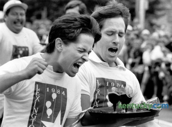 James Baker, left, and David Trice react after spilling a glass of wine in the waiter's race in downtown Lexington on July 4, 1984. The race was then part of Lexington's Fourth of July celebration. Baker and Trice, representing the Lafayette Club, were in first place and were about 20 feet from the finish line when their glass toppled over. Lexington's 2016 Fourth of July festival will be held Monday. Photo by Gary Landers  | Staff
