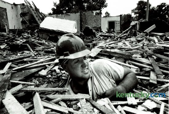 "Willis Bastin emerged from the floor of a house he was tearing down on Central Avenue in Lexington on June 26, 1985. Bastin, 23, quit his noon to 8pm job driving a forklift and established his own demolition company, W.N. Bastin Contracting Company. He was razing three houses at 614, 618 and 622 Central Avenue. The Lexington-Fayette County Historic Commission called them ""turn-of-the-century T-plan cottages"" built between 1895 and 1900. Photo by Ron Garrison 