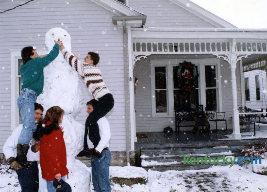 Alex Heim, top left, got a lift from his brother Kevin and John Heim, top right, got a lift from Tony Smith while Alesia Smith supoervised the building of their snowman, Dec. 25, 1993. The five were putting the finishing touches on the 9-foot-tall snowman on Park Avenue in Lexington, which celebrated the white Christmas, but later paid for it as the snow turned to ice overnight makming travel difficult. Photo by Mark Cornelison | staff