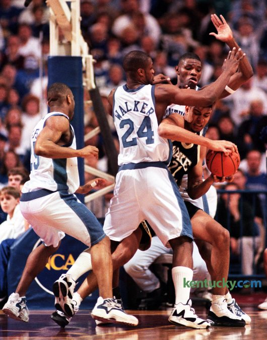 """University of Kentucky's Antoine Walker and Walter McCarty helped double-team Wake Forest's Tim Duncan, as Anthony Epps, left, stood by to help in during the Cats' 83-63 win in the NCAA Midwest Regional Finals in Minneapolis on March 23, 1996. Frustrating Duncan consistently with aggressive traps and double teams, UK limited the Wake star to two field goals. So effective was the Cat defense that Duncan, a junior, did not score a field goal until 12 minutes remained in the contest. """"They did a great job on me,"""" the ACC Player of the Year said. """"They were very aggressive double teaming and trapping. They probably played me better than anyone has done all year."""" Kentucky would go on to win their sixth national title nine days later. Duncan, a 5-time NBA champion retired Monday, July 11, 2016 after 19 seasons in the league. Photo by Mark Cornelison 