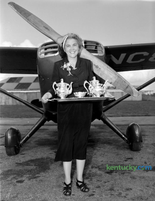 Portrait of Mrs. Greenwood Cocanougher standing in front of a small airplane, holding a silver tea set; August 1950.  She was awarded the tea set after winning the Jane Lausche Air Safety Trophy in the Powder Puff and Beau Derby, an efficiency race for women from Columbus, Ohio to Boston. Published in the Lexington Herald August 29, 1950. Herald-Leader Archive Photo